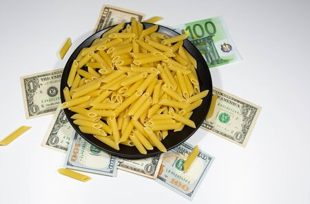 Pasta on a black plate under which lies money dollars Stock Photo