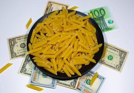 Pasta on a black plate under which lies money