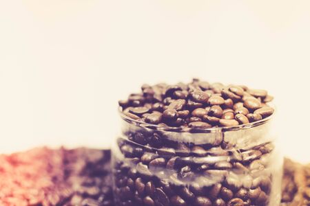 Coffee beans in a can among scattered coffee beans in a retro image
