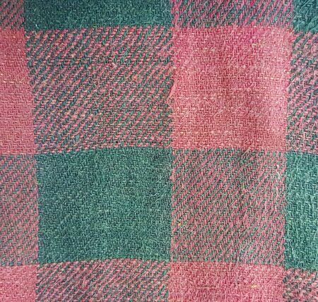 Old faded decrepit red-black checked fabric with thick threads texture