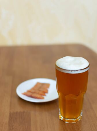 Beer in a glass on a wooden table and a plate with fish