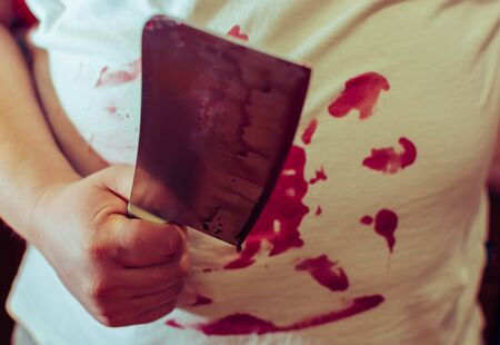 An ax knife in blood, in the hands of a man, clothes in blood