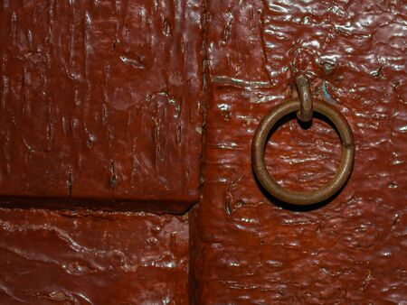 Ring for attaching a padlock in an old red painted door.