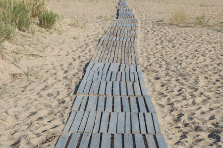 A tropical path made of boards across the sandy beach to the sea. Imagens