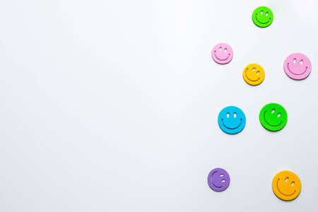 Multicolored icons of smiling emoticons on white paper 版權商用圖片