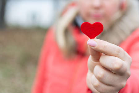 The girl holds out a heart in her hand as a sign of love.