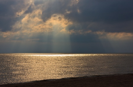 sunset on the beach, dark clouds and the reflection of sunlight on the water Stock Photo