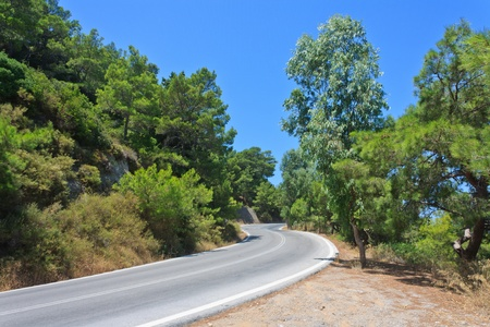 asphalt road between the hills and trees Stock Photo