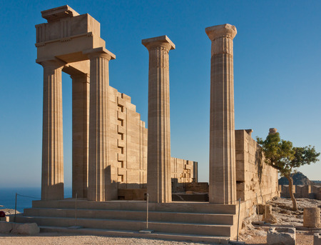 Ancient Greek acropolis. Front view of the columns and walls. near the tree grows.