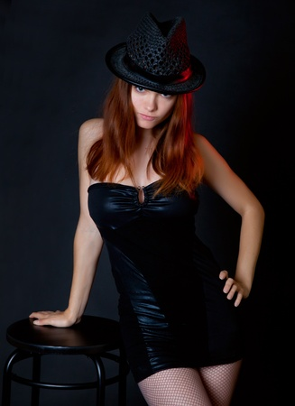 Young woman with hat is standing near a stool  Black background photo