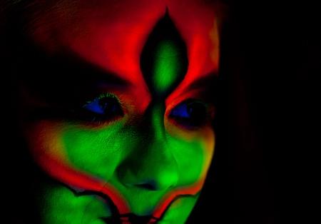 body paint: Woman s face with fluorescent bodyart  Black background  Studio shot