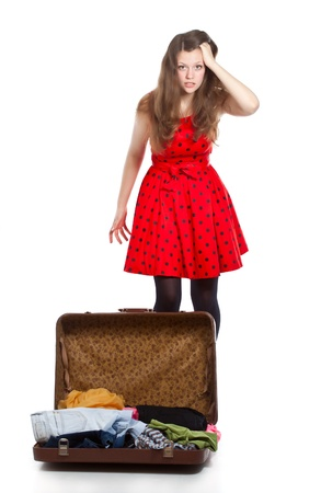 Young teenage girl with an opened suitcase  Studio shot  Isolated on white photo