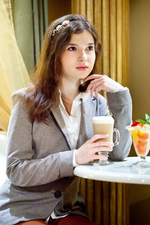 Young brunette woman is drinking coffe in a cafe photo