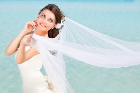 Giovane sposa bruna vicino al mare blu Archivio Fotografico - 13687799