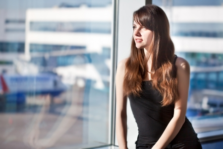 Young brunette woman is waiting to departure in the airport Foto de archivo