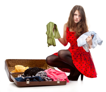 Young teenage girl with an opened suitcase  Studio shot  Isolated on white