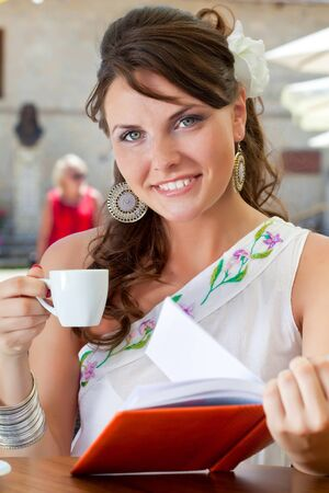 Young brunette woman is drinking coffee and reading book in a cafe photo