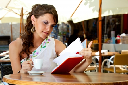 Young brunette woman is drinking coffee and reading book in a cafe