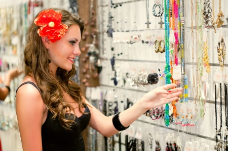 Young woman is choosing jewerly in the shop photo