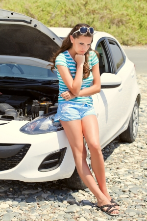 bad accident: Young brunette woman is standing near broken car