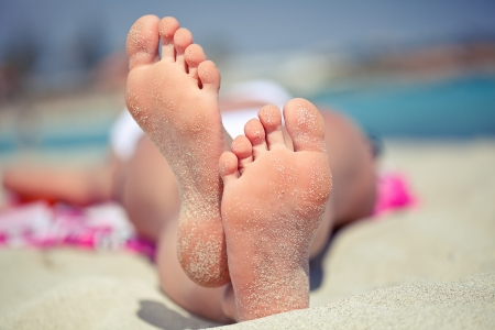 Woman s feet on the white sand near the sea  Stock Photo