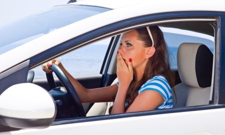 A scared beautiful woman is in the car Stock Photo