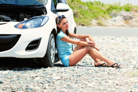 Young tired woman is sitting on the road near the car photo