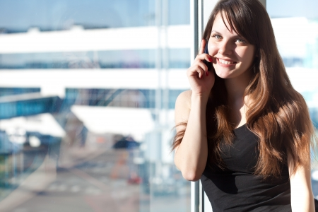 Young brunette woman is talking on mobile phone in the airport photo