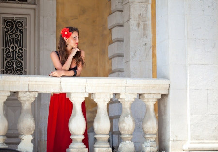 Pretty spanish woman is standing on the balcony photo