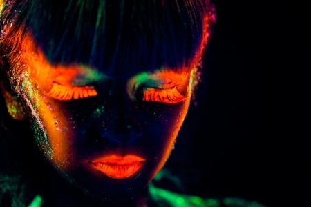 Woman s face with fluorescent bodyart  Black background  Studio shot
