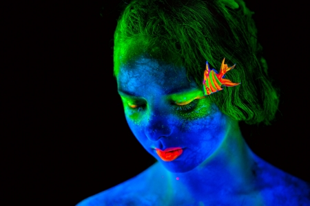 bodypaint: Woman s face with fluorescent bodyart  Black background  Studio shot