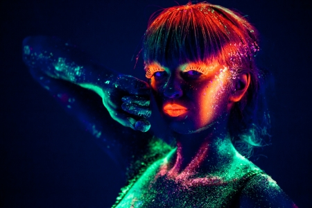 body paint: Woman s face with fluorescent bodyart  Black background  Studio shot