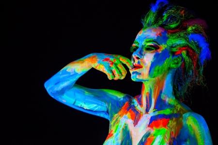 body paint: Mujer s cara con bodyart de tiro fluorescente fondo Negro Studio Foto de archivo