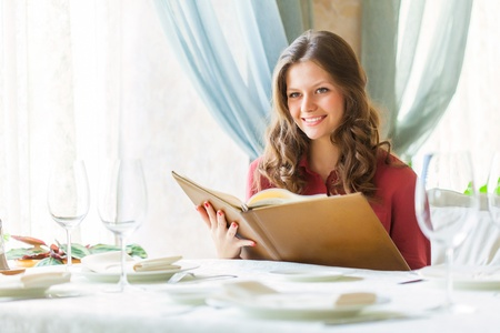 A smiling woman in a restaurant with the menu in hands photo