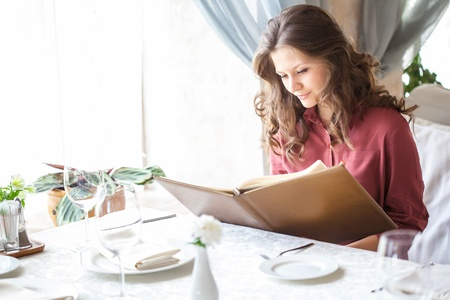 Una donna sorridente in un ristorante con il menu in mano Archivio Fotografico - 15315133
