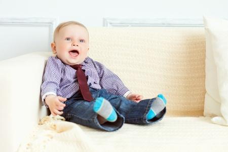 0 1 months: Boy in suit is sitting on sofa  Studio shot