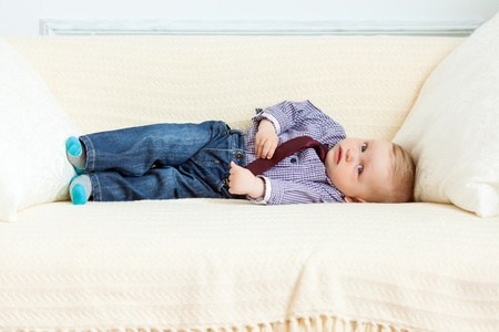 0 6 months: Boy in suit is lying on sofa  Studio shot
