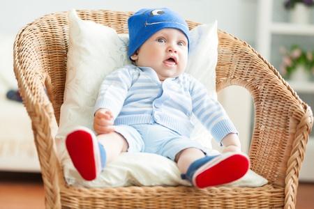 0 1 months: Boy is sitting on armchair  Studio shot