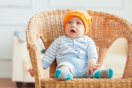 0 6 months: Boy is sitting on armchair  Studio shot