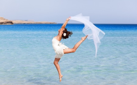 Woman in white dress is jumping near the sea photo