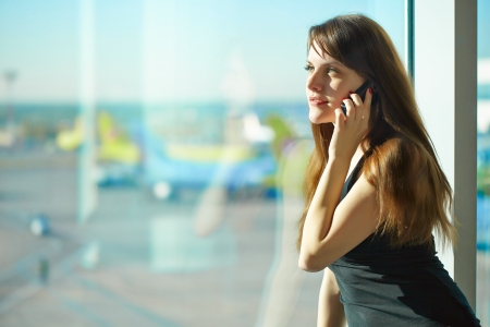 Young brunette woman is talking on mobile phone in the airport Foto de archivo
