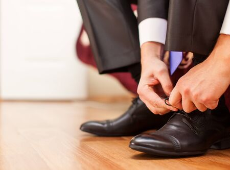 tying: Man is tying his black shoes. Close-up