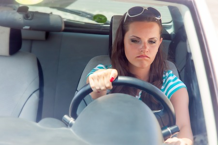 woman driving car: Young woman is trying to turn the broken car on Stock Photo