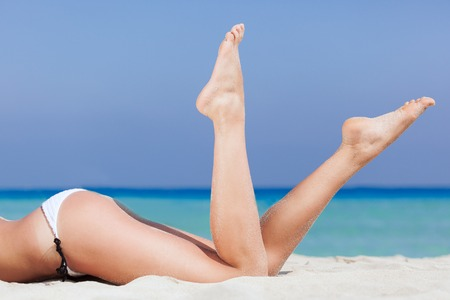 Woman is lying on the beach. Legs close-up photo