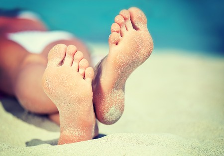 Womans feet on the white sand near the sea.