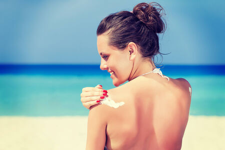 woman barefoot: A smiling woman is applying sunblock on the beach Stock Photo