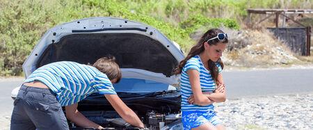 Man and woman near their broken car photo