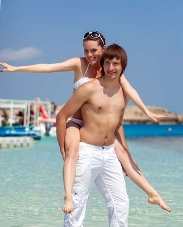 Happy young couple is having fun on the beach photo