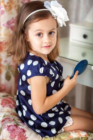 Little girl in blue dress is hairbrushing photo