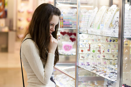 rapturous: Young woman is choosing jewerly in the shop